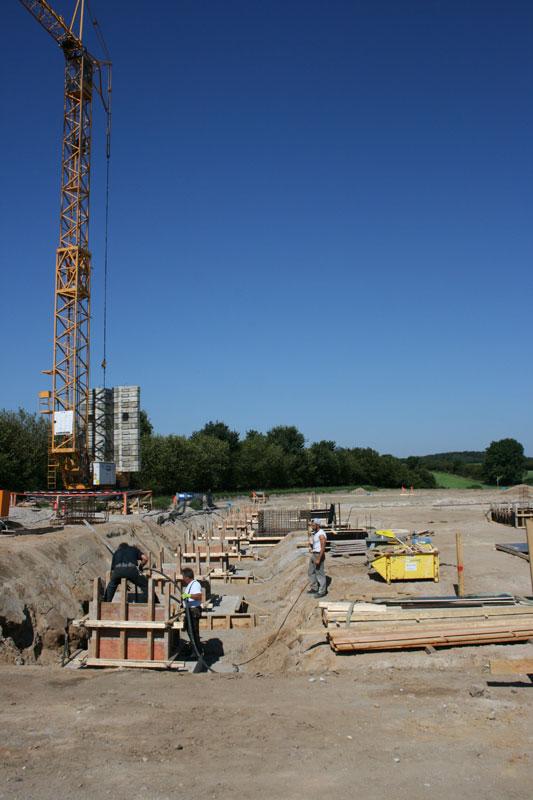 Süd-West Seite der zukünftigen Fundamentreihe. Der Beton wird direkt nach dem Einbringen mit einem Rüttler verdichtet.