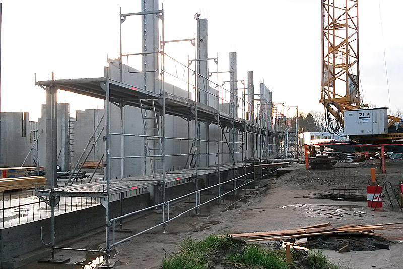Die Halbfertigteile der Außenwand auf der Westseite sind aufgestellt und eingerüstet.