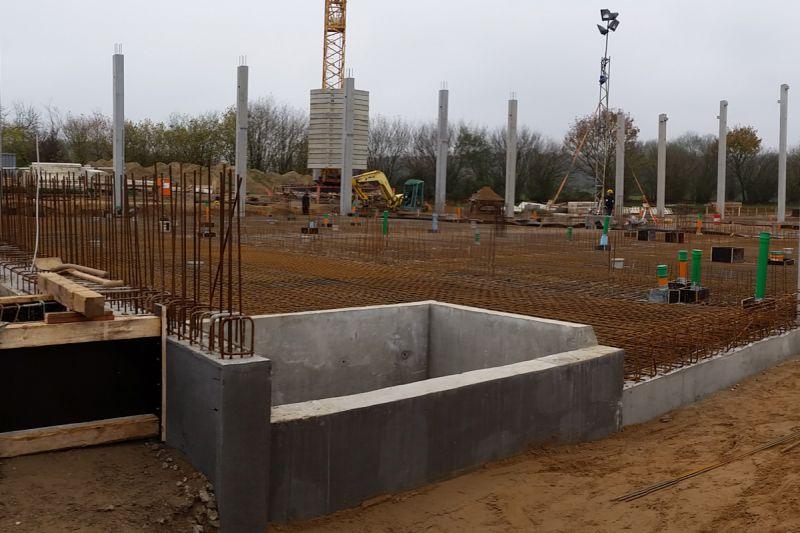Links neben der Milchannahmegrube werden die Verschalungen für die Fundamente des Kopfbaus gebaut. Rechts daneben, auf der Sauberkeitsschicht, ist die Bewehrung schon eingebracht.